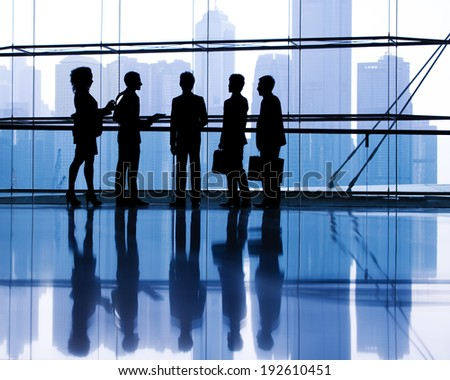 Silhouettes of business people discussing in an office. - stock photo