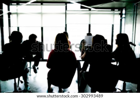 Silhouettes of Business People Having Board Meeting. Blur or Defocus image. - stock photo