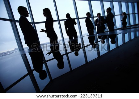 Silhouettes of business people interacting in board room  - stock photo
