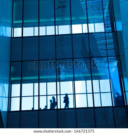 silhouettes of business people rushing at morden office building. - stock photo