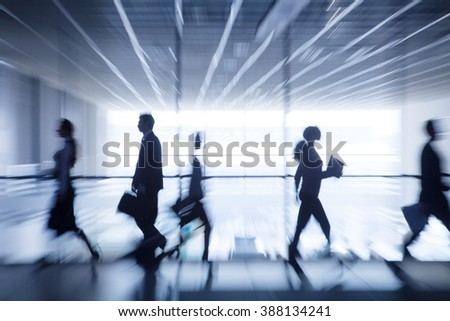 silhouettes of business people rushing for the large windows in the background - stock photo