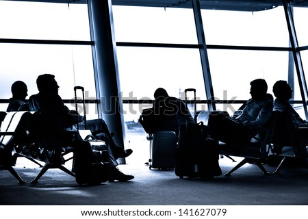 Silhouettes of business people traveling on airport; waiting at the plane boarding gates. - stock photo