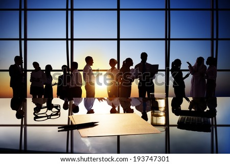 Silhouettes of Business People Working in Board Room - stock photo