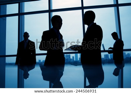 Silhouettes of business people working in the office - stock photo