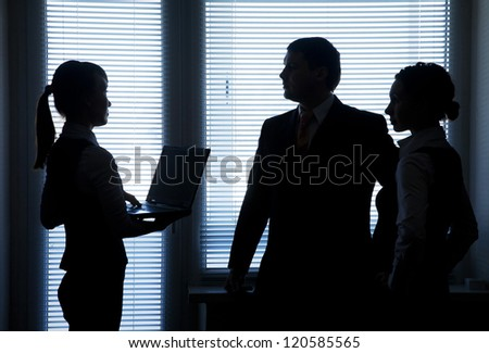 Silhouettes of business team talking on the background of the window in the office - stock photo