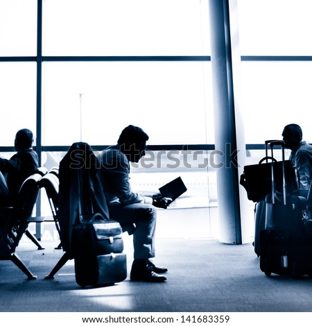 Silhouettes of businessman traveling on airport; waiting at the plane boarding gates. - stock photo