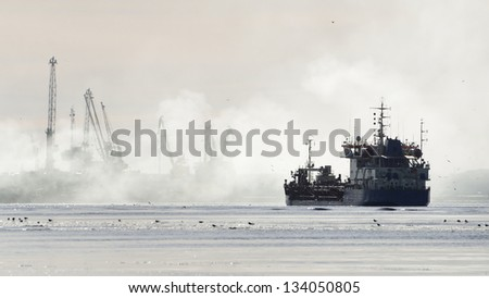 silhouettes of cargo ship and port cranes in fog - stock photo