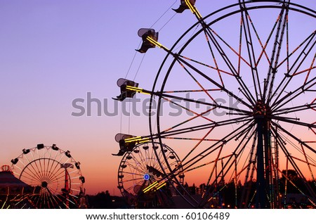 Silhouettes of carnival rides under sunset - stock photo