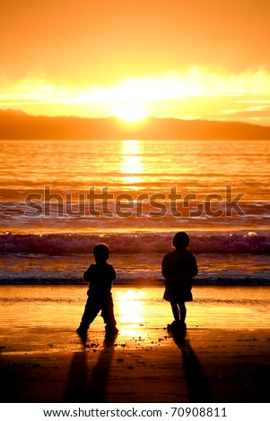 Silhouettes of Children Playing at Sunset - stock photo