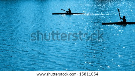 Silhouettes of children, rowing on blue water  on paddles - stock photo