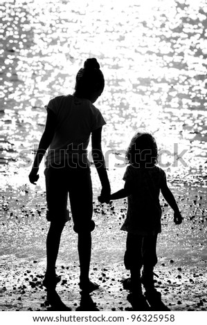 Silhouettes of children standing on seacoast in sunshine