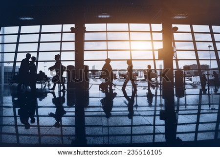 Silhouettes of commuters walking at airport - stock photo
