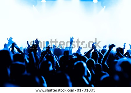 silhouettes of concert crowd in front of bright blue stage lights - stock photo