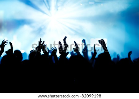 silhouettes of concert crowd in front of bright stage lights