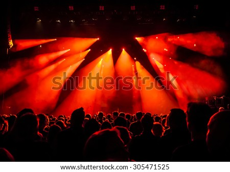 silhouettes of concert crowd in front of bright stage lights - a small depth of field signifies that the focused area is narrow - stock photo