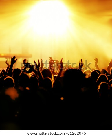 silhouettes of concert crowd in front of bright yellow stage lights - stock photo