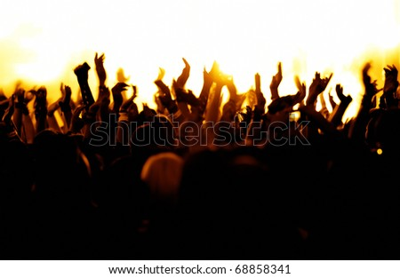silhouettes of concert crowd in front of bright yellow/white stage lights - stock photo