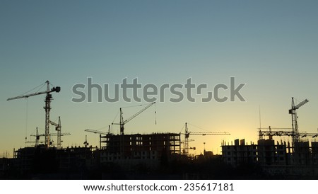 silhouettes of construction  and power lines at sunset - stock photo