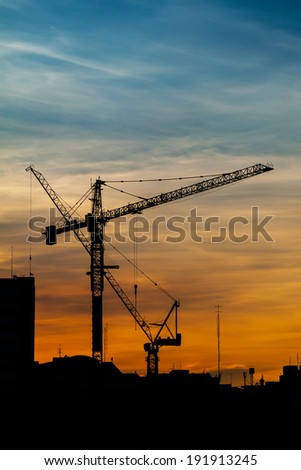 Silhouettes of construction crane in dusk against the twilight - stock photo