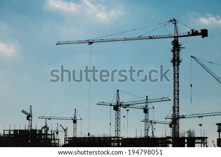 Silhouettes of construction cranes against a blue sky - stock photo
