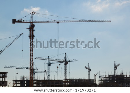 Silhouettes of construction cranes in the sky  - stock photo