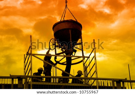 Silhouettes of construction workers pouring concrete mix at the building site over sunset sky - stock photo