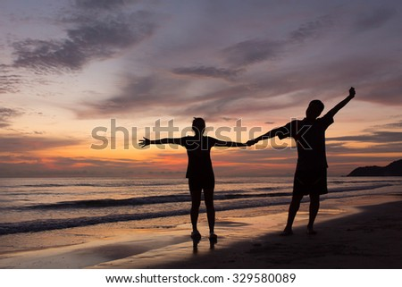 silhouettes of couple happy on the beach at sunset