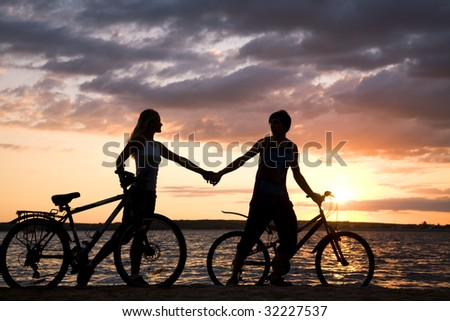 Silhouettes of couple holding each other by hands while walking down seashore with their bicycles at sunset - stock photo