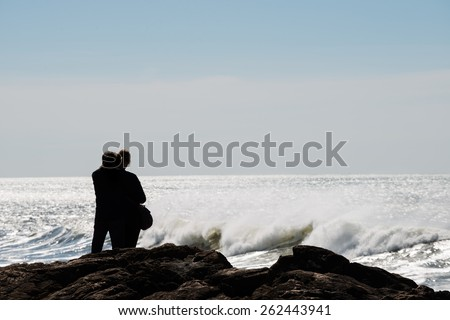 Silhouettes of couple in love standing and looking at waving ocean.Copy space, unrecognizable people - stock photo