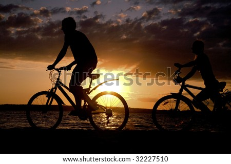 Silhouettes of couple riding their bicycles on seashore at sunset - stock photo
