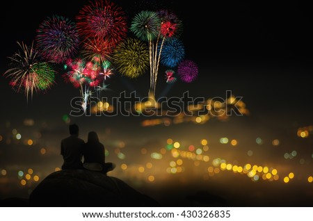 Silhouettes of couple sitting on rock. Watch the beautiful fireworks celebration at night. - stock photo
