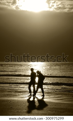 Silhouettes of couple walking along a beach at dramatic sunset and talking. Crisis in relations background. Aged photo. Sepia. - stock photo