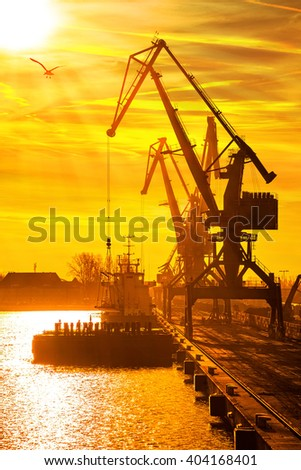 Silhouettes of cranes and ship in port of Gdansk, Poland.