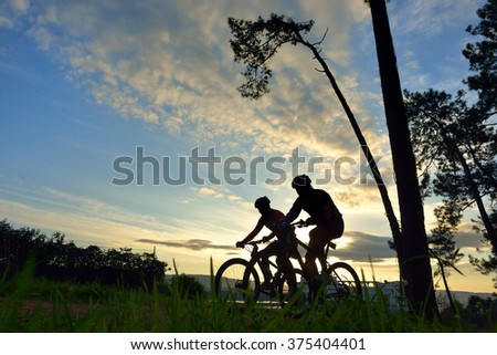 silhouettes of cyclists in a race through the woods at dawn - stock photo