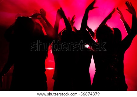 Silhouettes of dancing people having a celebration in a disco club, light is shining through the silhouettes of people - stock photo