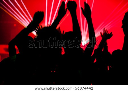Silhouettes of dancing people having a celebration in a disco club, the light show is sending laser beams through the backlit scene - stock photo