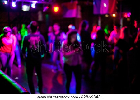 Silhouettes of dancing people in a club in front of bright scenic lights concept of disco, night life. Blurred people are dancing in a night club with original bokeh lights in the background.