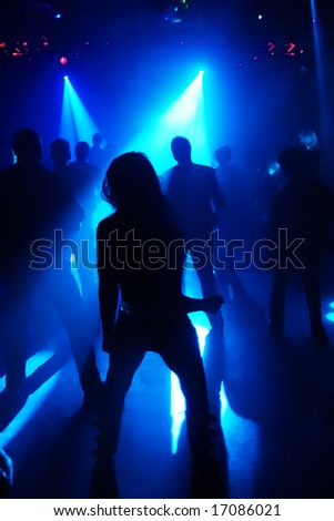 silhouettes of dancing people in a disco - stock photo