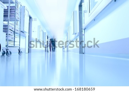 Silhouettes of doctors in the corridor of a modern hospital - stock photo