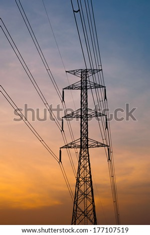 silhouettes of electricity post  with sunset sky background - stock photo
