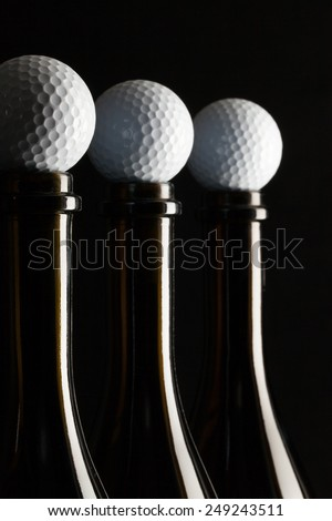 Silhouettes of elegant wine bottles with golf balls on a black background - stock photo