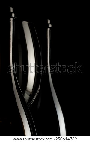 Silhouettes of elegant wine glasses and a wine bottles on a black background