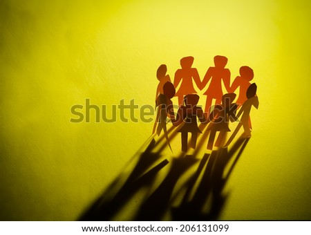 Silhouettes of exited people standing in circle -isolated in yellow background - stock photo