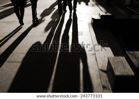 silhouettes of family on the cobblestone pavement at sunset, sepia color tone