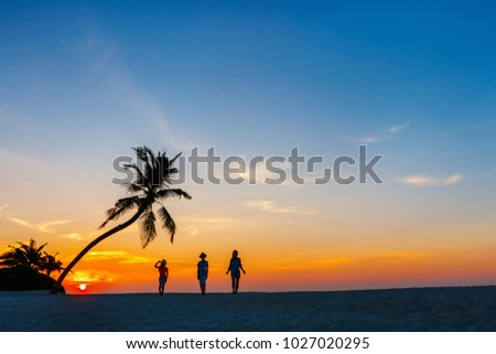 Silhouettes of family with two kids at tropical beach during sunset