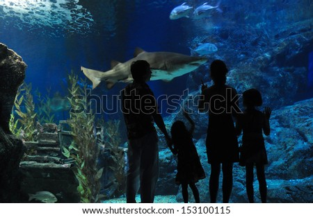 Silhouettes of family with two kids in oceanarium  - stock photo