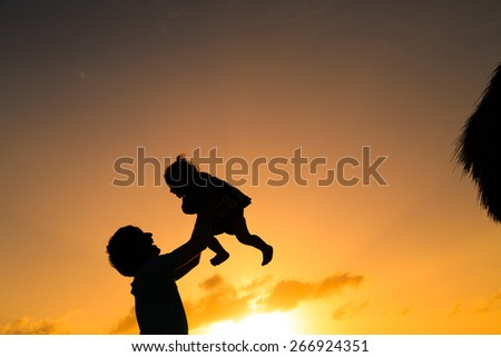 silhouettes of father and little daughter playing at sunset - stock photo