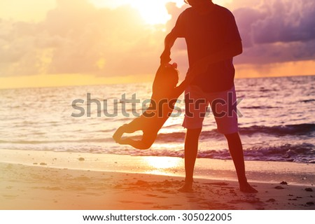 silhouettes of father and little daughter playing at sunset beach - stock photo