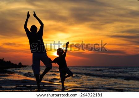 silhouettes of father and son doing yoga at sunset sea