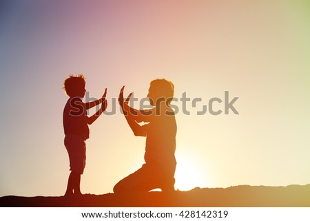 silhouettes of father and son having fun at sunset - stock photo